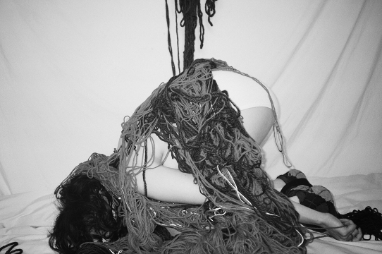 Black and white photograph of the artist Zoe Forsyth's body covered in yarn