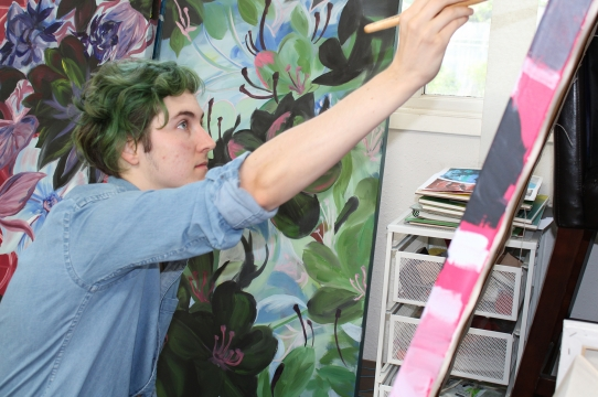 Artist Connor Alexander with a work in progress painting