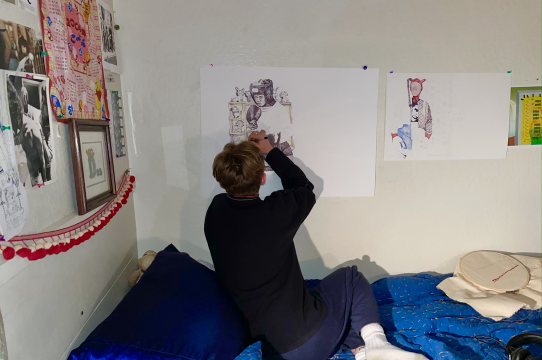 Artist Lucinda Gold working on drawing on their studio wall