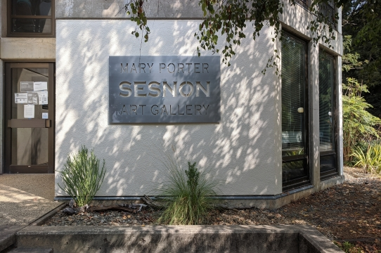 A metal sign of the Mary Porter Sesnon Art Gallery at Porter College, surrounded by green plants